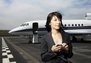 Thoughtful businesswoman holding phone while standing against corporate jet on runway - CAVF00862
