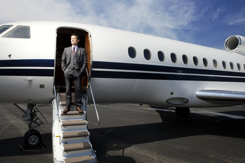 Businessman standing on steps of corporate jet - CAVF00865