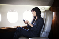 Businesswoman using phone while traveling in corporate jet - CAVF00868