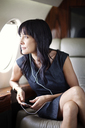 Businesswoman listening music while looking through window in corporate jet - CAVF00874
