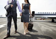 Low section of business couple holding hands while walking on airport runway - CAVF00877