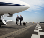 Businessmen walking towards corporate jet - CAVF00880