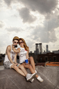 Happy young couple taking selfie on building terrace against cloudy sky - CAVF00904