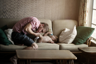 Father kissing baby boy's feet on sofa at home - CAVF00919