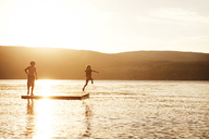 Sister diving into lake while boy standing on floating platform during sunset - CAVF00978