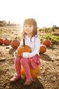 Portrait of cute girl sitting on pumpkin at field - CAVF01008