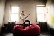 Young woman playing electric guitar on bean bag at home - CAVF01056