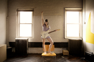 Happy woman playing guitar while standing on chair at home - CAVF01059