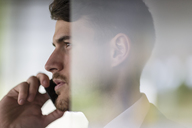 Close up profile serious businessman talking on smart phone, looking away - CAIF04602