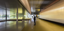 Businessman texting with smart phone in illuminated modern office lobby corridor - CAIF04605
