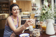 Smiling young woman texting with smart phone at breakfast table - CAIF04671