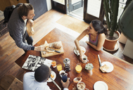 Friend roommates and eating breakfast and drinking coffee at table - CAIF04674
