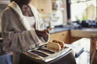 Woman texting with smart phone, toasting bread in toaster in kitchen - CAIF04677