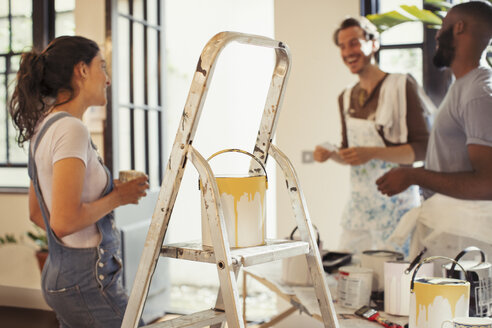 Friends drinking coffee and painting living room - CAIF04689