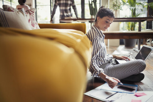 Female freelancer working at laptop on living room floor - CAIF04716