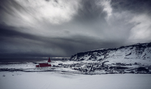 Church in remote snow covered landscape below stormy sky, Vik, Iceland - CAIF04743