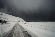 Road through snow covered landscape below stormy sky, Vik, Iceland - CAIF04746