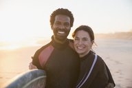 Portrait smiling, confident multi-ethnic couple with surfboard on sunny summer sunset beach - CAIF04767