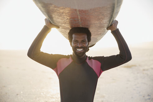 Portrait smiling, confident male surfer carrying surfboard overhead on sunny summer beach - CAIF04785