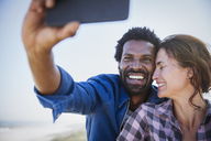 Affectionate, happy multi-ethnic couple taking selfie with camera phone - CAIF04788