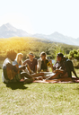Young friends hanging out, playing guitar and enjoying picnic in sunny summer grass - CAIF04809