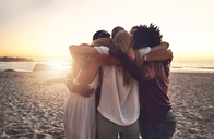 Young friends hugging in a huddle on sunset summer beach - CAIF04818