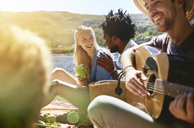 Young friends playing guitar and enjoying sunny summer picnic - CAIF04824