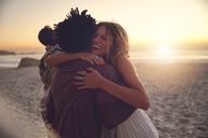 Affectionate couple hugging on sunny sunset summer beach - CAIF04836
