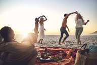 Young couples dancing, enjoying picnic on summer beach - CAIF04839