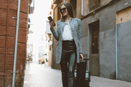Young businesswoman in the city checking cell phone - OCAF00167