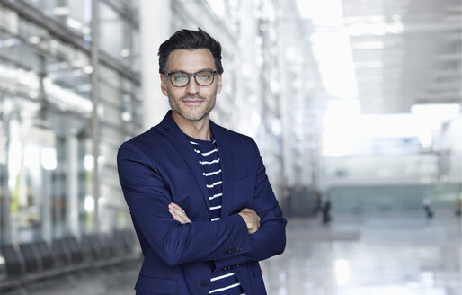 Portrait of stylish businessman with stubble wearing blue suit and glasses - PNEF00553