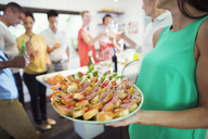 Woman serving tray of food at party - CAIF04843