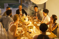 Friends eating together at dinner party - CAIF04864