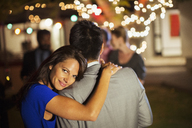 Couple hugging at party - CAIF04879