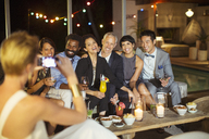 Woman taking picture of friends at party - CAIF04885