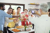 Man taking picture of friends at party - CAIF04891
