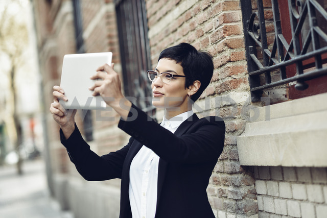 Smiling young businesswoman taking selfie with tablet - JSMF00060