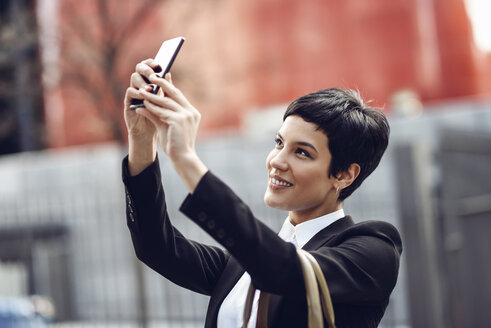 Portrait of smiling young businesswoman taking selfie with cell phone - JSMF00063