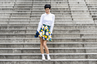 Fashionable young woman wearing skirt with floral design standing on stairs - JSMF00069