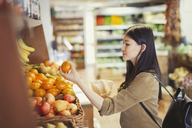 Young woman shopping, examining oranges in grocery store - CAIF04986