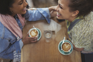 Young affectionate female friends drinking coffee and laughing in cafe - CAIF04998