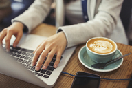 Hands of young woman using laptop, drinking cappuccino in cafe - CAIF05004