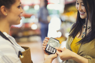 Female customer with credit card using contactless payment in store - CAIF05016