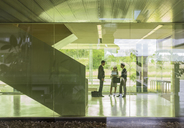 Business people talking in modern office lobby - CAIF05037