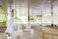 Scientist in clean suit using digital tablet at window - CAIF05043