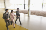 Business people walking in office lobby - CAIF05046