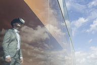 Businessman using virtual reality simulator glasses at modern window with cloud reflection - CAIF05052