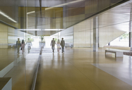 Business people walking in modern office lobby corridor - CAIF05061