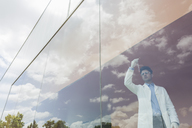 Scientist examining liquid in beaker at modern window with cloud reflections - CAIF05064