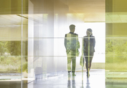Silhouette business people walking in modern office corridor - CAIF05073